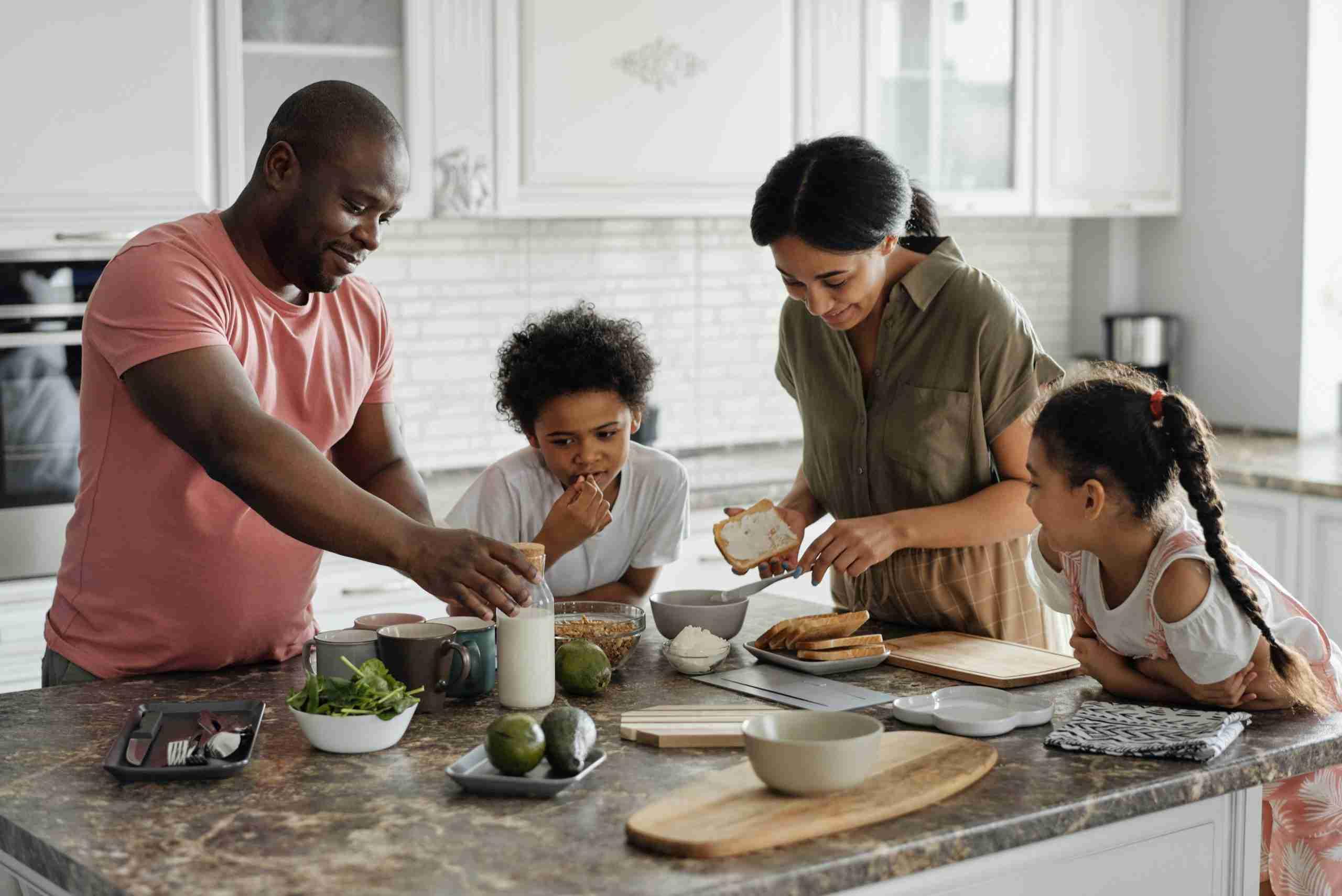 Family preparing food around bench